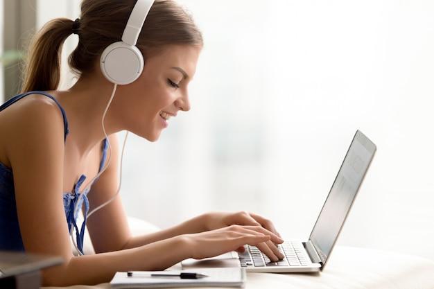 Mujer en auriculares aprendiendo idioma en línea Foto gratis