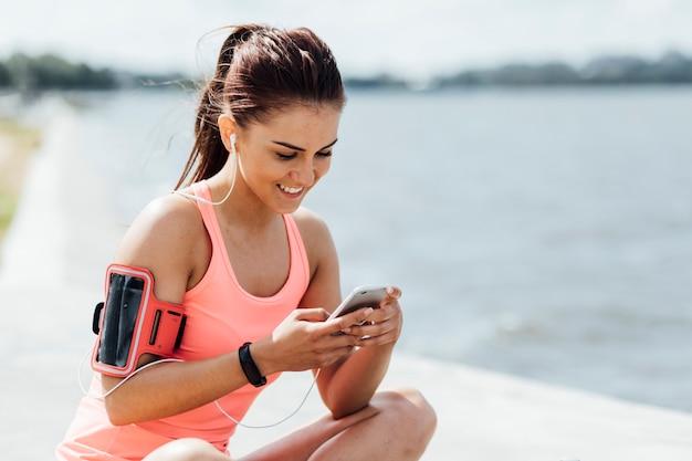 Mujer con auriculares revisando su teléfono Foto gratis