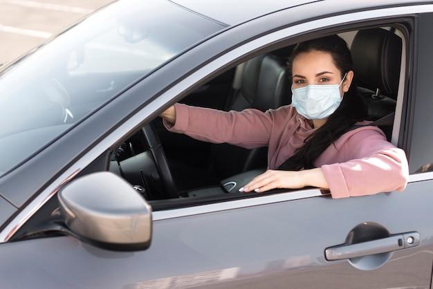 Mujer en el auto con máscara de protección Foto Premium