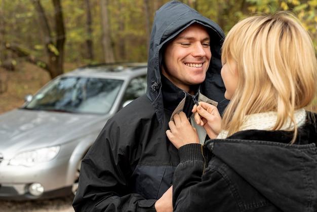 Mujer ayudando a cerrar la chaqueta del marido Foto gratis