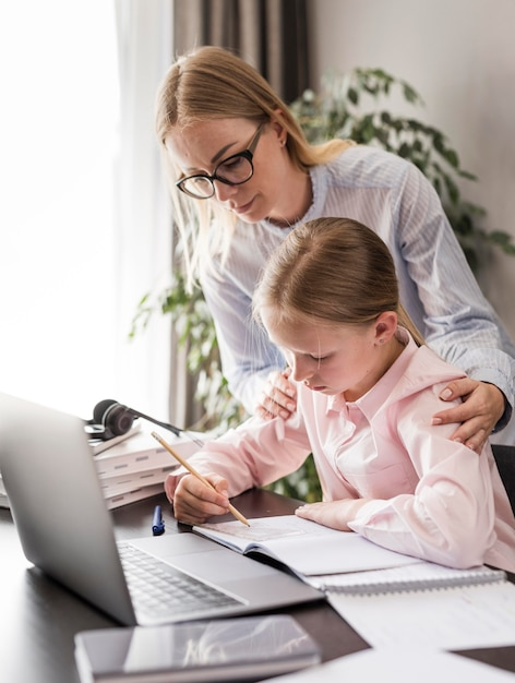 Mujer ayudando a una niña haciendo su tarea Foto gratis
