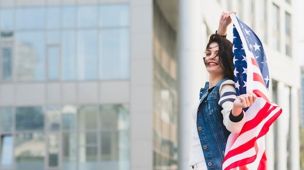 Mujer con bandera americana en calle de la ciudad Foto gratis