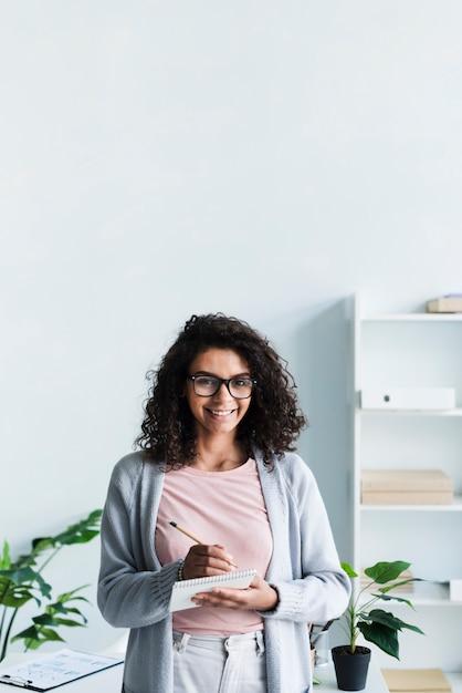 Mujer bastante joven con la libreta en oficina Foto gratis