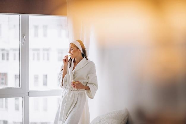 Mujer en bata de baño junto a la ventana y comiendo cereal Foto gratis