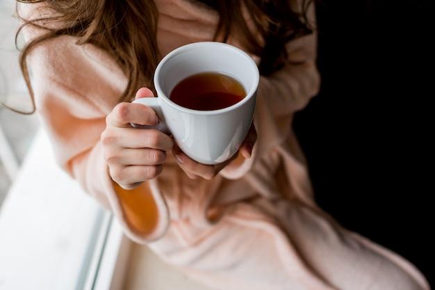 Mujer en bata de baño sosteniendo una taza de té caliente. estado de ánimo de otoño. Foto gratis
