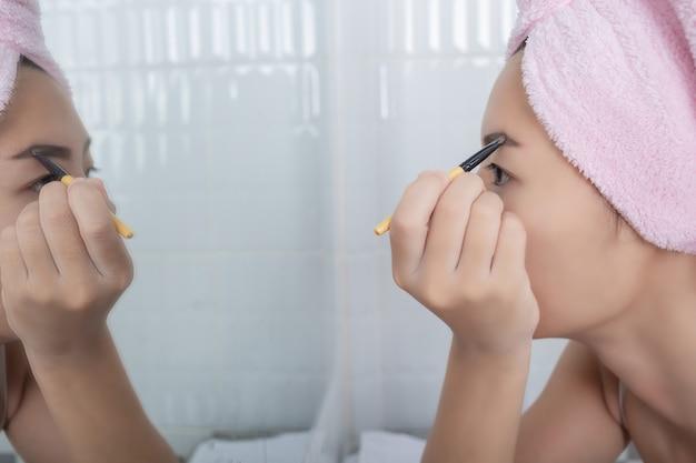 Mujer de la belleza que aplica maquillaje. Foto gratis