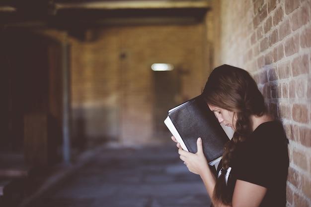 Mujer con la biblia contra su cabeza mientras reza Foto gratis