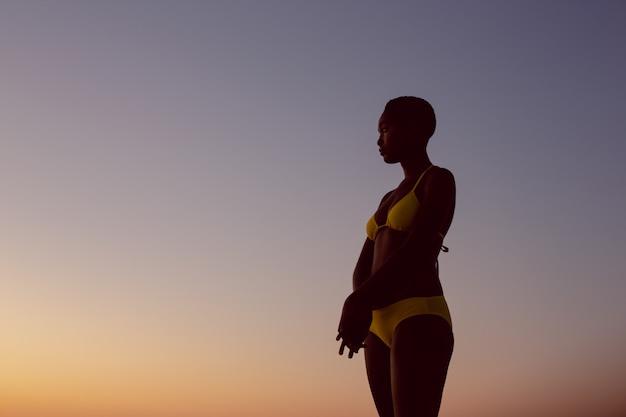 Mujer en bikini de pie en la playa Foto gratis