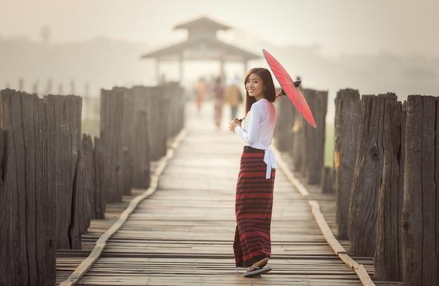 Mujer birmana sosteniendo un paraguas rojo tradicional y caminando sobre el puente u bein, myanmar Foto Premium