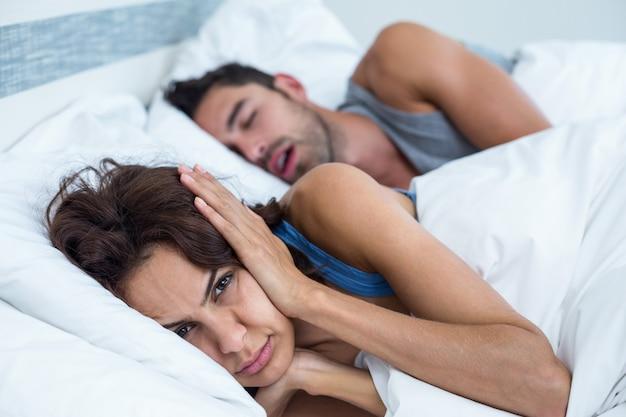 Mujer bloqueando las orejas con las manos mientras el hombre roncando en la cama Foto Premium