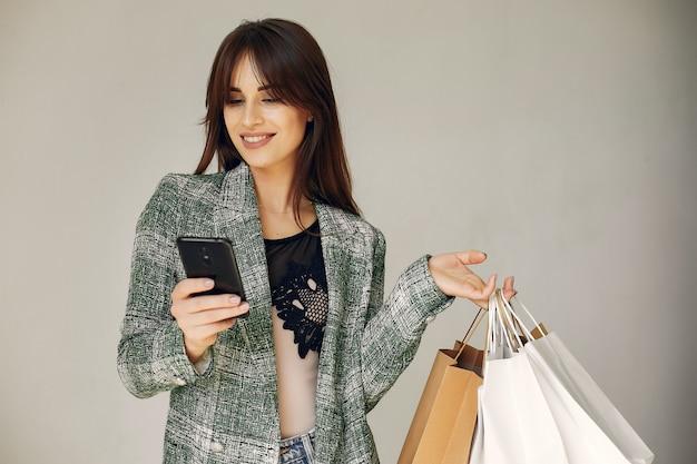 Mujer con bolsas de compras sobre un fondo blanco. Foto gratis