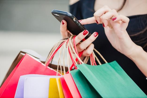 Mujer con los bolsos de compras que sostienen el smartphone Foto Premium