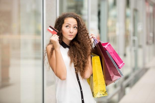Mujer bonita con bolsas de compras y mostrando tarjeta de crédito en blanco Foto gratis