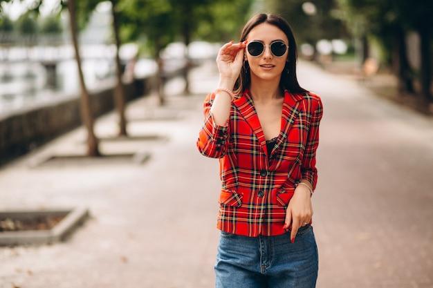 Mujer bonita en chaqueta roja afuera en el parque Foto gratis