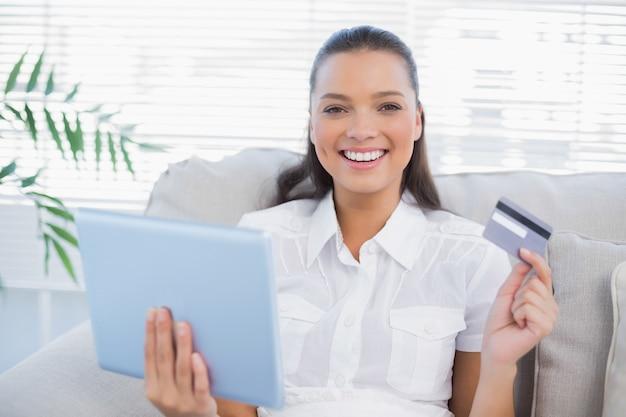 8e8f606a3ed85 Mujer bonita feliz comprando en línea usando su pc de la tableta ...