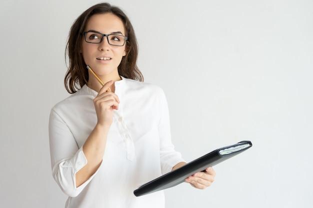 Mujer bonita joven pensativa que sostiene el fichero y el lápiz Foto gratis