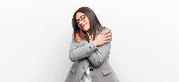 Mujer bonita joven que se siente enamorada, sonriente, abrazando Foto Premium