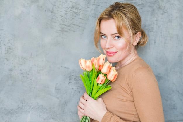 Mujer bonita de pie con ramo de tulipanes Foto gratis