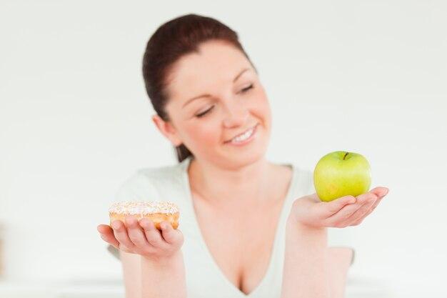 Mujer bonita posando mientras sostiene una dona y una manzana verde a1452781396f