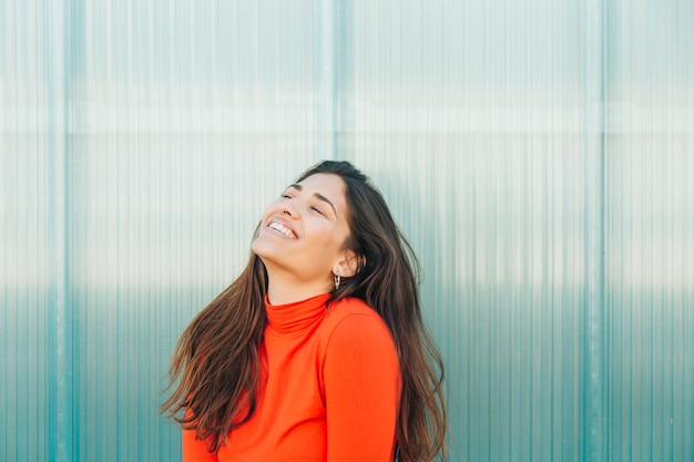 Mujer bonita que ríe contra el contexto metálico Foto gratis