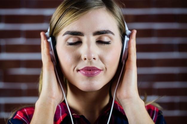 Mujer bonita rubia escuchando música Foto Premium