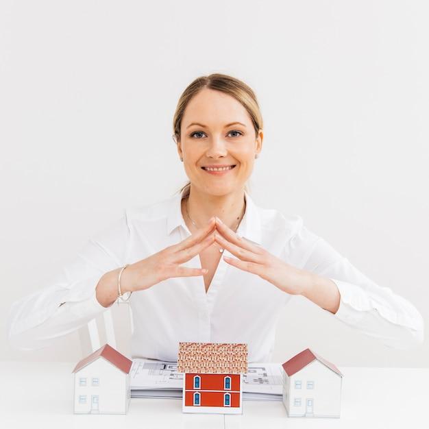 Mujer bonita sonriente que da seguridad a la casa modelo en el lugar de trabajo Foto gratis