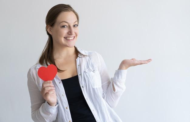 Mujer bonita sonriente que sostiene el corazón de papel y el espacio vacío Foto gratis