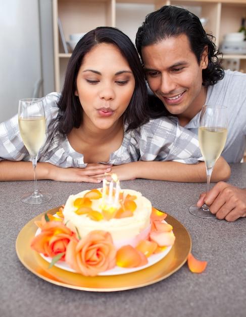Mujer bonita soplando velas con su esposo por su cumpleaños Foto Premium
