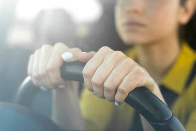 Mujer borrosa sosteniendo sus manos en el volante Foto Premium