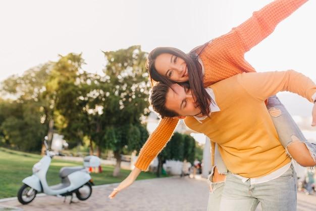Mujer bronceada en suéter divertido posando con novio no lejos de scooter Foto gratis