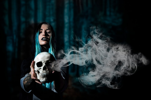 Mujer con cabello azul sosteniendo una calavera con humo Foto gratis