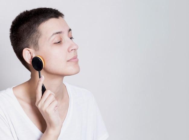 Mujer con cabello corto limpiando su cara con un cepillo Foto gratis