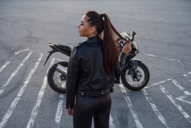 Mujer con cabello largo en una chaqueta de cuero en un estacionamiento subterráneo en una motocicleta Foto Premium