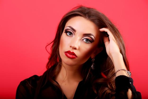 Mujer con cabello rizado oscuro que fluye y piel perfecta en rojo Foto Premium