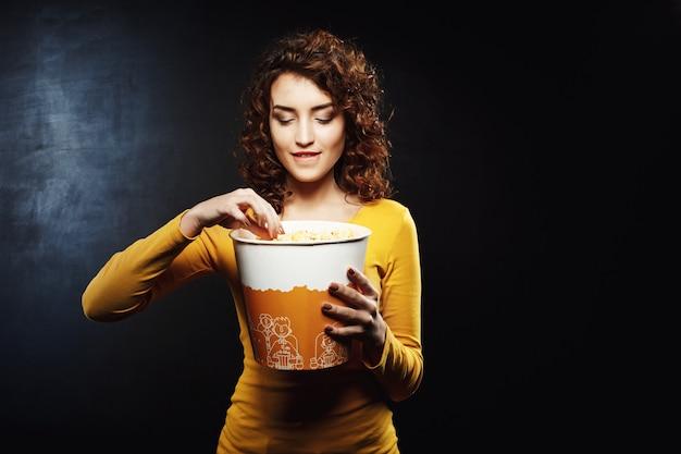 Mujer con cabello rizado toma palomitas de maíz mordiendo su parte inferior Foto gratis