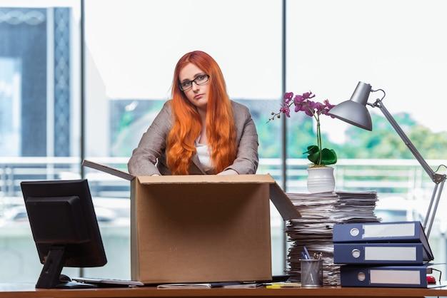 Mujer cabeza roja mudarse a la nueva oficina de embalaje sus pertenencias Foto Premium