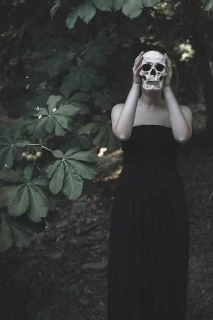 Mujer con calavera blanca en matorral Foto gratis