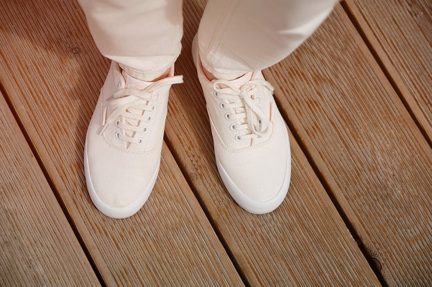 Una mujer en calzado deportivo se encuentra en la acera o en el pavimento de madera. piernas de una niña en nuevas zapatillas blancas y jeans. estilo de vida a la moda y con estilo. Foto Premium