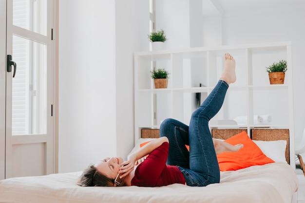Mujer en cama hablando por smartphone Foto gratis