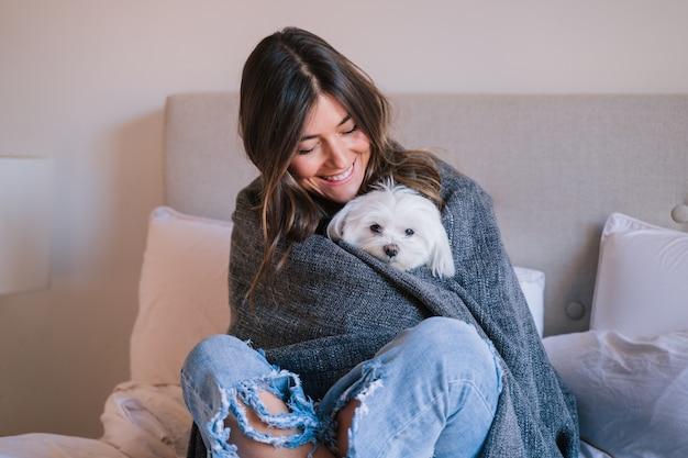 Mujer en la cama en su casa envuelta en una manta con su lindo perro maltés Foto Premium