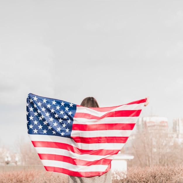 Mujer caminando con bandera americana Foto gratis
