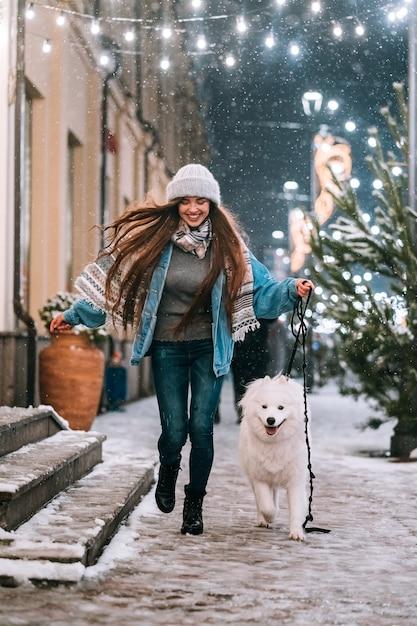 Mujer caminando con perro blanco Foto gratis