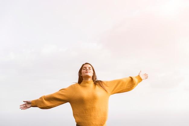 Una mujer caminante con los brazos extendidos disfrutando del aire fresco contra el cielo. Foto gratis