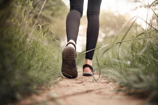 Mujer caminante caminando por camino de tierra Foto gratis
