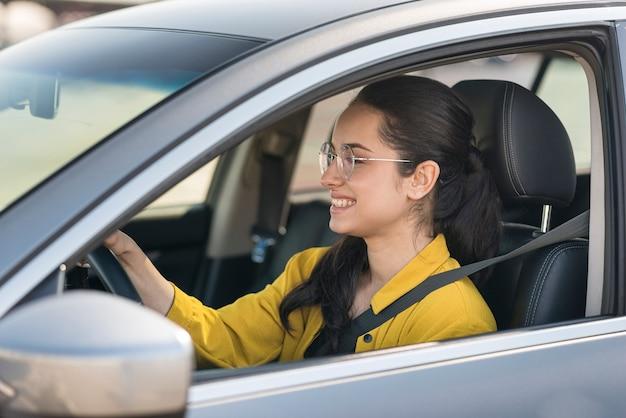 Mujer en camisa amarilla conduciendo Foto gratis