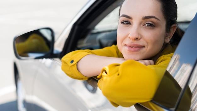Mujer en camisa amarilla sentada en el auto Foto gratis
