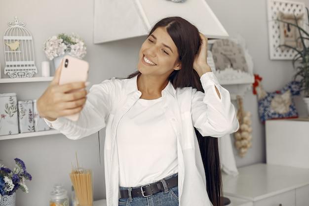Mujer en una camisa blanca de pie en la cocina y haciendo una selfie Foto gratis