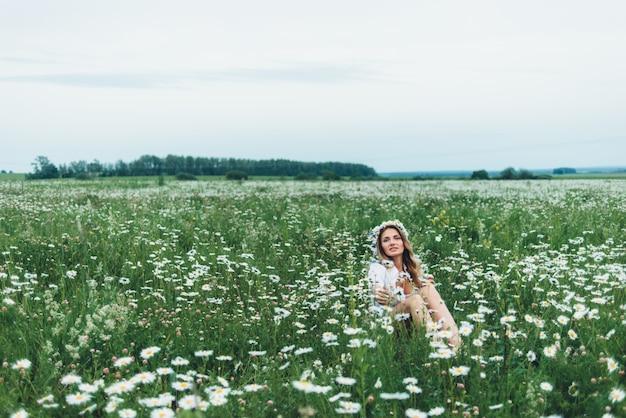 Una mujer en un campo de manzanillas Foto Premium