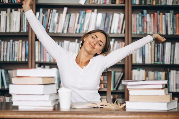 Mujer cansada estirando en la biblioteca Foto gratis