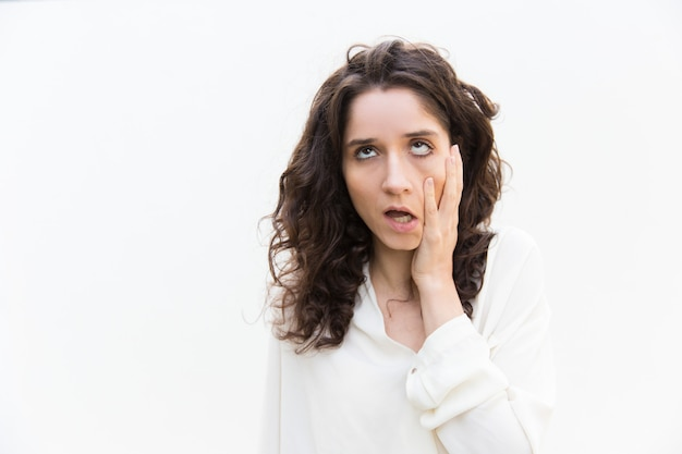Mujer cansada molesta tocando la mejilla, mirando hacia arriba Foto gratis
